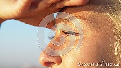 Retrato muy cercano de mujer guapa rubia que mira al sol, cierra los ojos con la mano y pinta Brillante metrajes