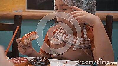 Retrato niño lindo mordiendo y masticando donut dulce con acristalamiento de caramelo en panadería Cierra a un cocinero que come  almacen de metraje de vídeo