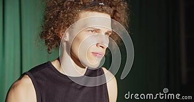 Retrato rizado del jugador de baloncesto listo sombra grave luz brillante juega oscuridad la confianza mira almacen de metraje de vídeo