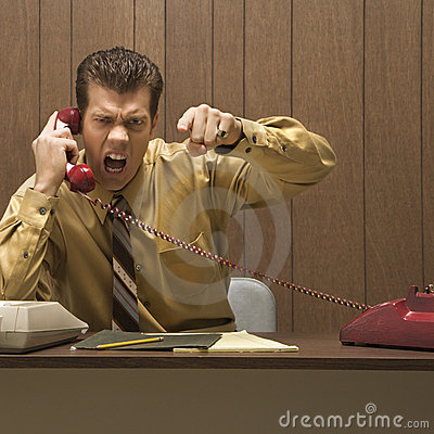 Retro business scene of angry man at desk.