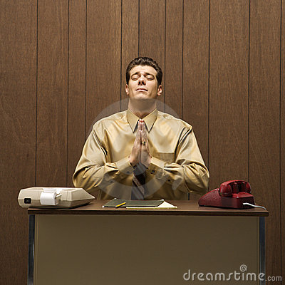 Retro business scene of man praying at desk.