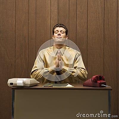 Retro business scene of man praying at desk.