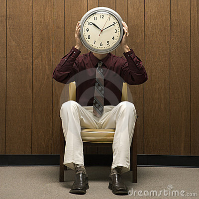 Retro businessman holding clock over face.