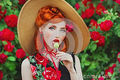 Retro girl with red lips in a dress with a print of roses with yellow lollipop on summer background. Young redhead model in a hat Stock Photo