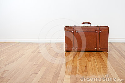 Retro leather suitcase on wooden floor