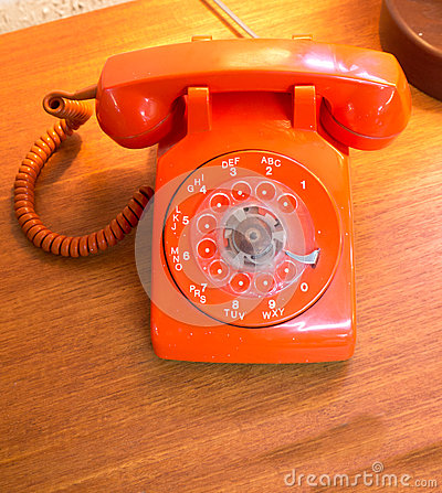 Retro orange rotary dial telephone.
