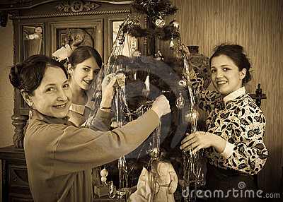 Retro photo of girls with mother at Christmas tree