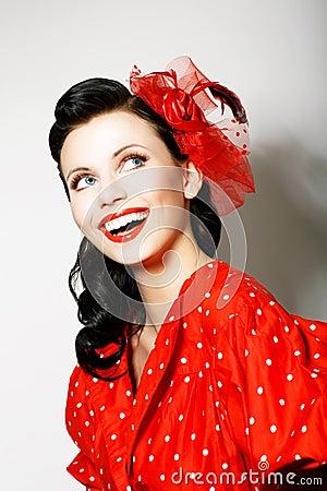 Retro stile. Esaltazione. Ritratto della donna sorridente a trentadue denti felice nel Pin sul vestito rosso