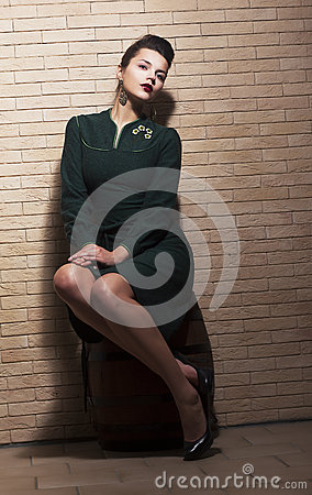 Retro Style. Pin-up Girl sitting in Green Dress on Barrel over Brick Brown Wall