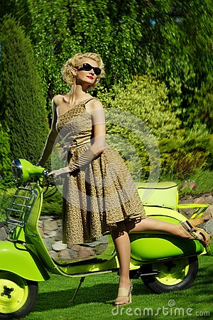 Retro woman outdoors with a green scooter