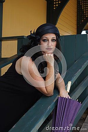 Retro Woman at Train Depot Holding Umbrella