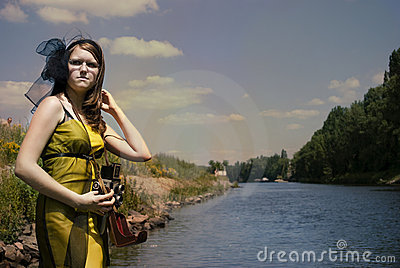 Retro young woman  with camera near the river