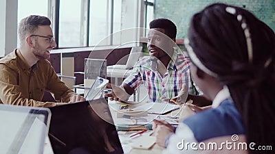Reunião criativa da equipe do negócio no escritório moderno Grupo de raça misturada de jovens que discutem ideias start-up, rindo filme