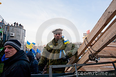 Revolutioner in national Pakistan hat guards the barricades on anti-government demonstration during the week of pro-EU protest Editorial Stock Image