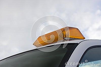 Revolver de advertência ambarino ilumina-se em um telhado de servic