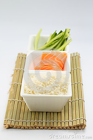 Rice salmon and sliced cucumber in white dish on bamboo mat
