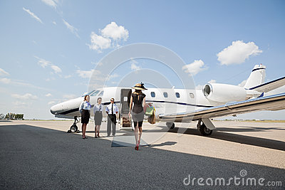 Rich Woman Walking Towards Private Jet At Airport