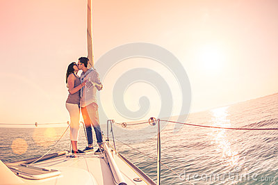 Rich young couple in love on sailboat cheering at sunset