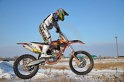 Rider on bike for motocross flies over hill