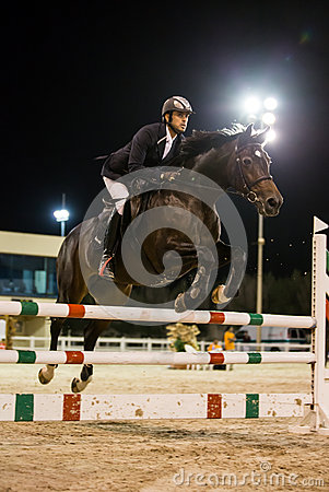 Rider competes in horse jumping competition Editorial Stock Image