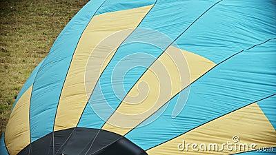 Riempiendo l'aerostato di aria calda facendo uso delle bande colorate gialle e blu della macchina del fuoco - sul pallone stock footage