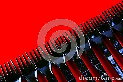 Riga delle forcelle di plastica su colore rosso