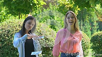 Rijke jonge vrouwen gooien dollars op camera, vreugde over een groot geldbedrag, prijs stock videobeelden