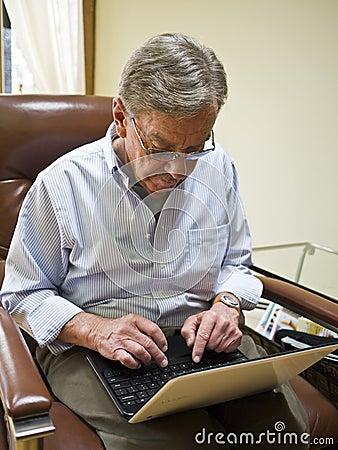 Rijpe mens die laptop met behulp van