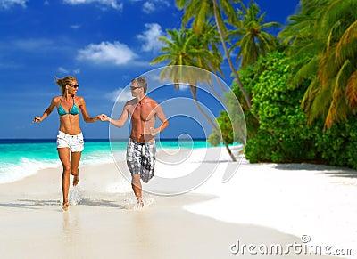 Rinnande par på stranden