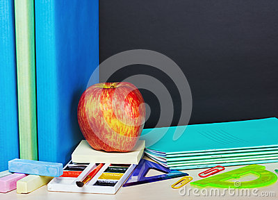 Ripe apple and school supplies