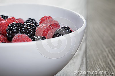 Ripe blackberries and raspberries in white bowl on old oak table