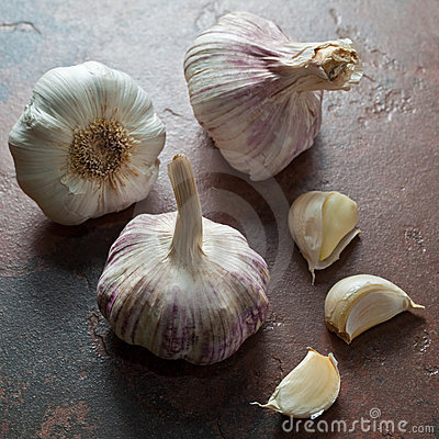 Ripe garlic bulbs with a couple of peeled cloves