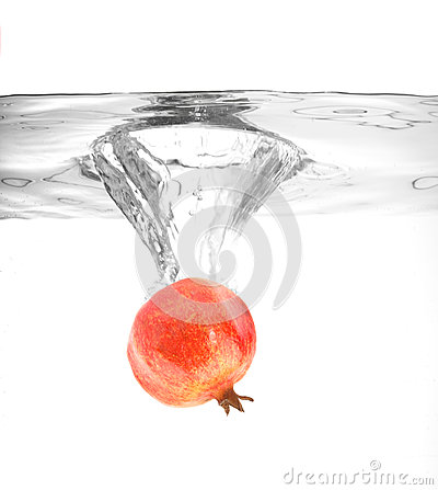 Ripe pomegranate falling into water