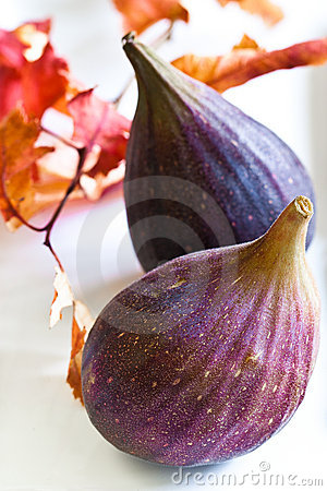 Ripe purple figs on a white plate