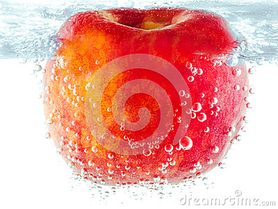 Ripe red apple with bubbles underwater