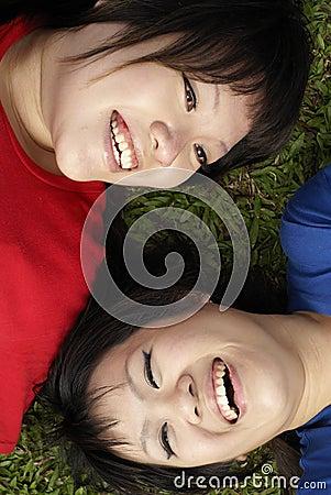 Riso adolescente asiático feliz de duas meninas