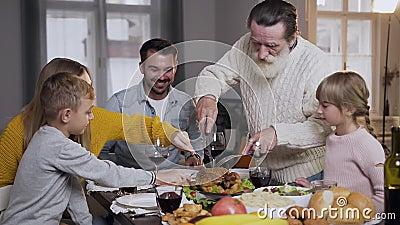 Rispettare il nonno anziano che scolpisce il tradizionale tacchino arrosto durante la festa del Ringraziamento video d archivio