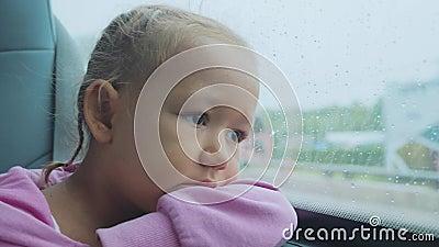 Ritratto del bambino triste che guarda fuori la finestra bagnata, mentre viaggiando in bus video d archivio