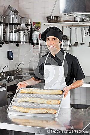 Cuoco unico maschio che presenta le pagnotte in cucina