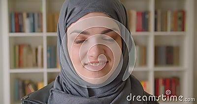 Ritratto del primo piano di giovane studentessa musulmana attraente nel hijab che sorride felicemente esaminando macchina fotogra archivi video