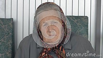 Ritratto del primo piano di una donna anziana in una bandana marrone stock footage