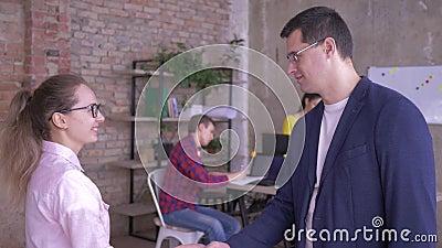 Ritratto del supervisore e di nuove mani di scossa degli impiegati su fondo degli impiegati di concetto alla tavola con i compute archivi video