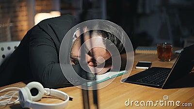 Ritratto dell'uomo bello stanco che dorme tardi sullo scrittorio in ufficio scuro alla notte archivi video