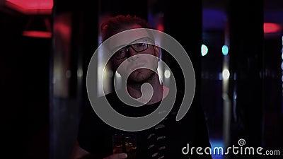 Ritratto della condizione triste dell'uomo con il vetro di alcool alla fine della discoteca su Uomo in vetri che esaminano macchi stock footage