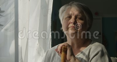 Ritratto della donna anziana triste che esamina il concetto della finestra all'interno di solitudine di depressione archivi video