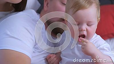 Ritratto di bambino sta dando da mangiare a casa a genitori uva di mamma e papà stock footage