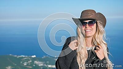 Ritratto di giovane donna europea di eleganza in cappello da cowboy ed occhiali da sole che sorride e che flirta video d archivio