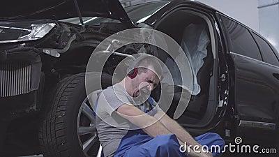 Ritratto di sbadiglio caucasico esaurito, appoggiato alla ruota e agli occhi di chiusura Professionista stanco in stock footage