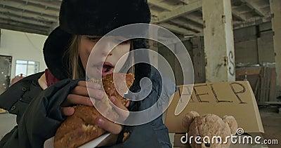 Ritratto di un rifugiato siriano con il volto sporco e gli occhi grigi che mangia avidamente il pane Ragazza senzatetto con cappe video d archivio