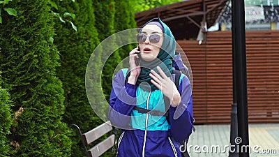 Ritratto di un turista della ragazza in un foulard e degli occhiali da sole con uno zaino che parlano sul telefono video d archivio